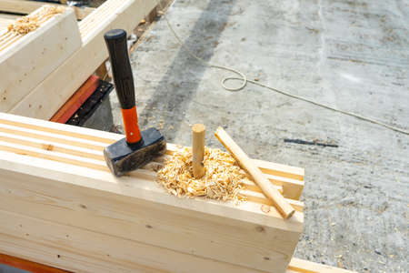 Construction of the house from a bar. Drilling holes and clogging of dowels. Stock Photo