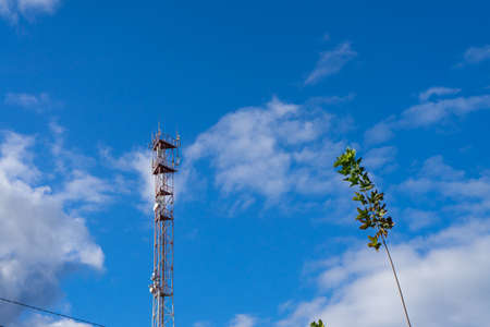 Antenna tower with blue sky and cloud background