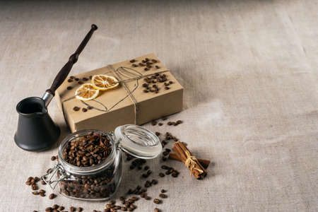 Cezve and roasted coffee beans in box on a rustic table, cinnamon and dried lemon Standard-Bild