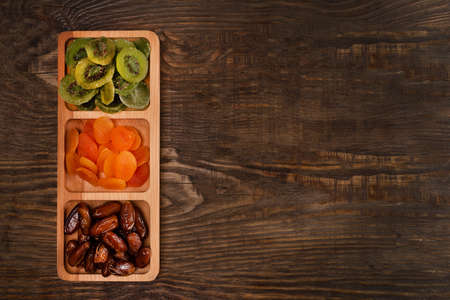 Dates, dried apricots and kiwis in a Compartmental dish on a dark wooden table