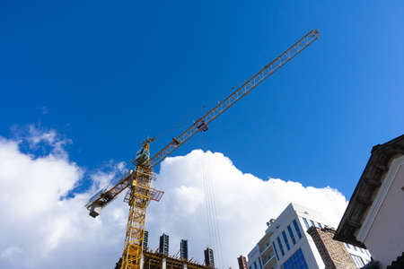 Building construction site with tower crane against blue sky