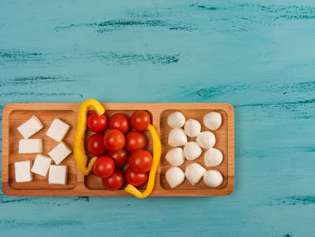 Cheese compartmental dish with different cheeses, on rustic wooden background