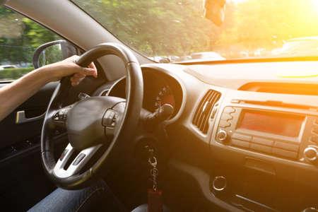 Una donna guida un'auto con una mano. Mano della donna che tiene con fiducia un volante. Mano sul volante donna alla guida di auto