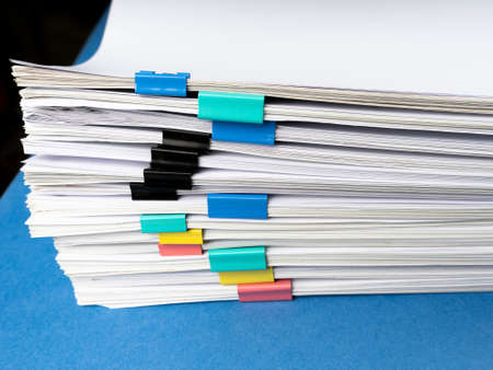 Mock up, stack of papers documents in archives files with paper clips on desk at offices, business concept.