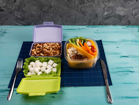Lunch box with appetizing food and on light wooden table.