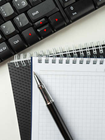 Office desk table with computer keyboard and supplies. On white background. Top view with copy space. Mock up