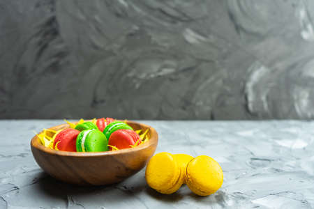 Colorful macaroons on stone table. Sweet macaroons in wooden dish.