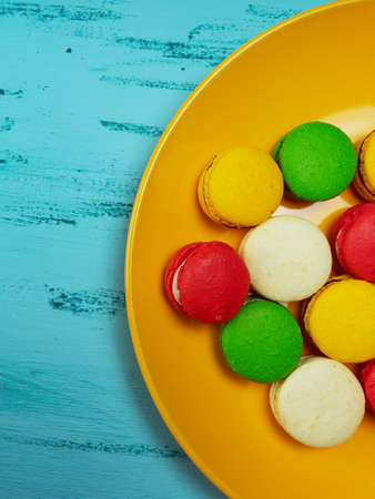 Colorful macaroons on yellow plate on wooden table.