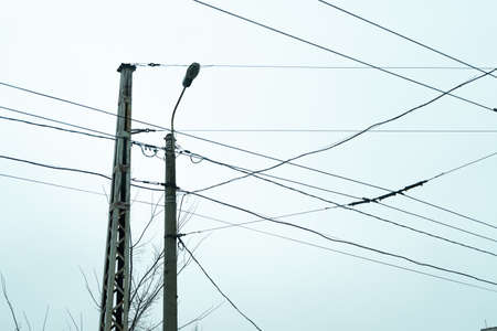 Old street light with many cables connected, isolated on gray sky. Copy space.