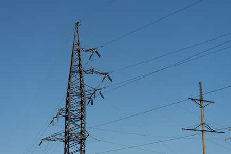 High voltage lines and power pylons in the industrial area on a Sunny day with a clear blue sky