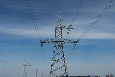 High voltage lines and power pylons on a sunny day with cirrus clouds in the blue sky.