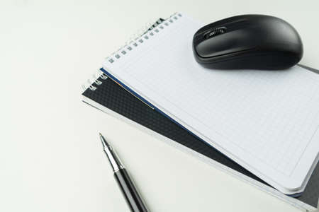 White wooden table with pen, mouse, notebook, . Workspace with copy space. Banco de Imagens