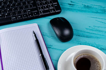 Office table desk. Workspace with note book, keyboard, office supplies and coffee cup on wooden background.