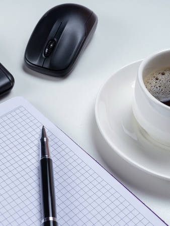 Office table desk. Workspace with blank note book, keyboard, office supplies and coffee cup on white background.