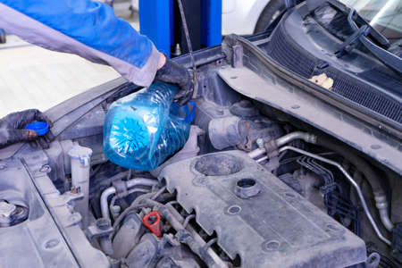 Car mechanic replacing and pouring fresh oil into engine with a special container at maintenance repair service station Banco de Imagens