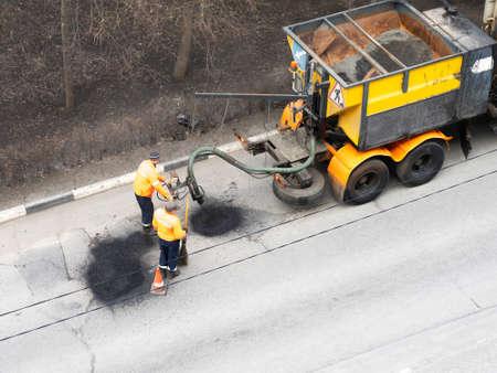 Aerial view of road workers repair asphalt covering. Teamwork concept Banco de Imagens