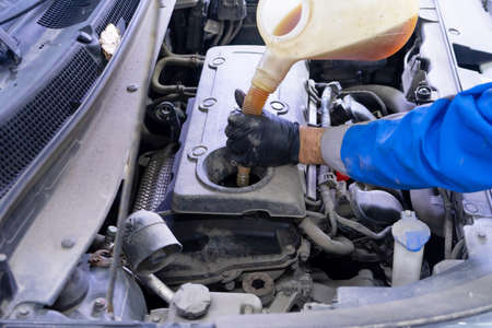 Car mechanic replacing and pouring fresh oil into engine with a special container at maintenance repair service station Stockfoto