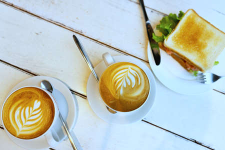 Bread sandwich with ham, cheese, cherry tomatoes, cucumber and lettuce and espresso coffee for breakfast. Selective focus
