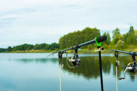 Carp fishing on beautiful blue lake with carp rods and rod pods in the summer morning. Fishing from the wooden platform