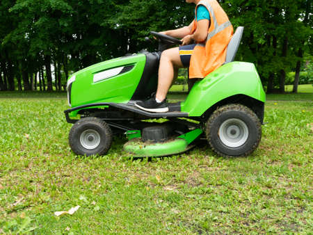 Professional lawn mower cuts the grass. Mowing in parks and residential areas.