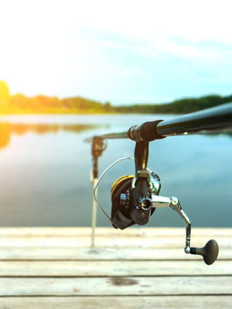 Carp fishing on beautiful blue lake with carp rods and rod pods in the summer morning. Fishing from the wooden platform. Stock Photo
