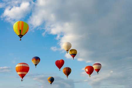 Colorful hot air balloons flying in blue sky. Few colorful, hot air balloons descending at the Balloon Festival