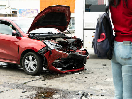 Pedestrians stand and look at the consequences of a car accident