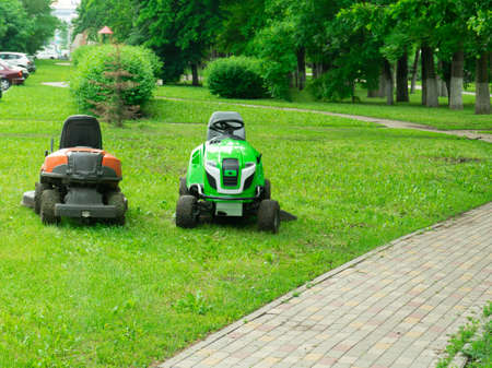 Professional lawn mower cuts the grass. Mowing in parks and residential areas 版權商用圖片