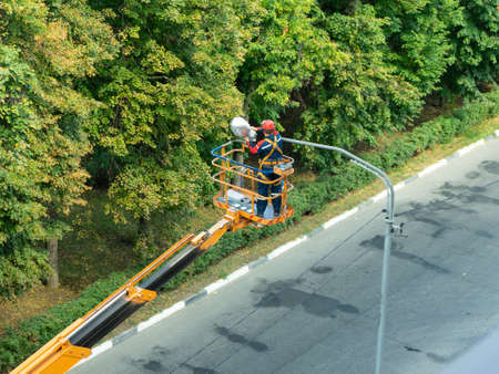 The specialist performs work on replacing old lamps on lampposts with new led lamps Foto de archivo