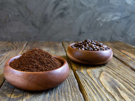 Ground coffee and coffee beans poured into wooden containers stand on a wooden table against a gray concrete wall