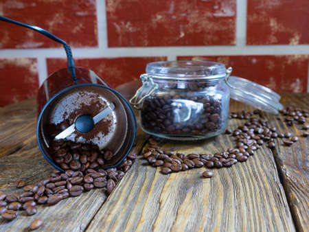 A coffee grinder with roasted coffee beans stands on a wooden table. coffee beans are scattered on the old wooden table top 스톡 콘텐츠