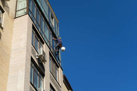 Industrial climbing. Climber wash windows in a high-rise building. Cleaning of windows glass elements 写真素材