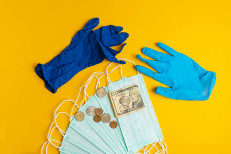 Medical masks, surgical gloves, banknotes and coins on a yellow background