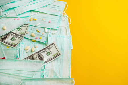 Sale of medical masks. Protective medical mask and different types of pills next to money on yellow background. Coronavirus concept. 2019 nCoV.