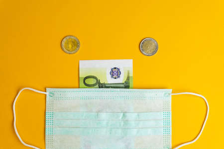Medical masks banknotes and coins on a yellow background. Archivio Fotografico