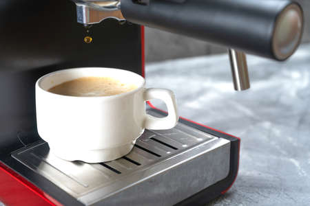 The last drop of coffee falls from the portafilter into the coffee Cup. Red coffee maker pouring hot espresso coffee in a white cup.