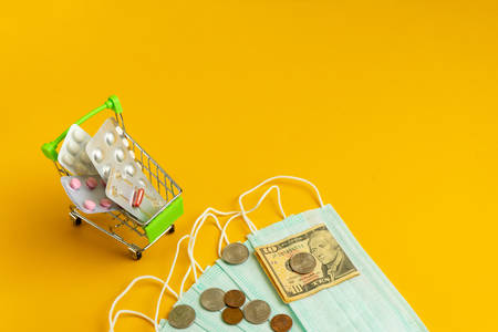 The concept of inflation in medicine. Medical masks, medicines and money on a yellow background.