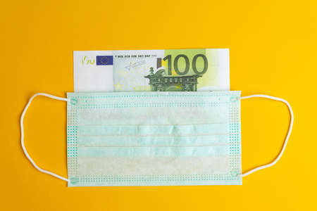 The medical mask covers the banknote. Concepts of protecting the currency and economy during the crisis.