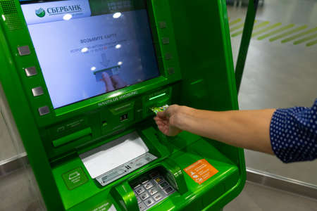 Hand inserting ATM credit card into bank machine to withdraw money Editoriali