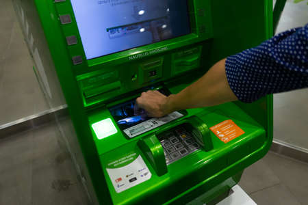 A woman's hand puts money in an ATM. Credit payment via ATM.