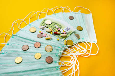 Sale of medical masks. Protective medical mask and different types of pills next to money on yellow background.The concept of inflation in medicine.
