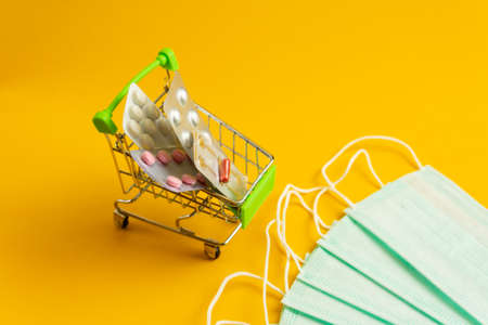 Cart with tablets and white medical masks on a yellow background. Concept protection against viruses and infections