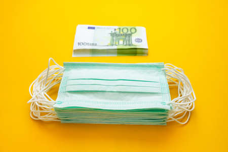 A stack of medical masks next to a stack of money on a yellow background. The concept of increasing the price of surgical masks due to the rapid spread of the coronavirus. Archivio Fotografico