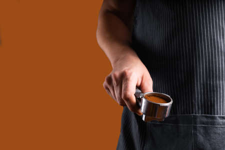 A man with a portafilter in his hands. The concept of making coffee in a coffee machine. Photo in a low key.