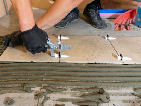 Workers are using plastic clamps and wedges to leveling the ceramic tile on the floor. Tile leveling system.