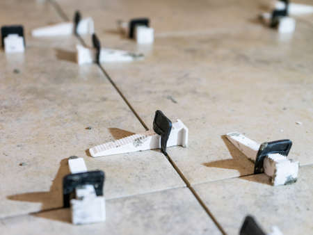 Tile levelling system with plastic clips and wedges. Close-up view, selective focus, blurred background.