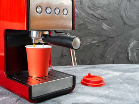 Red coffee machine fills a red paper cup. Coffee to go.