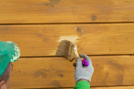A worker's hand in a glove, painting a wooden house. Covering a wooden house with a protective compound Фото со стока