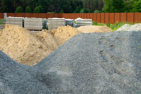 Piles of rubble and sand are stacked on the construction site