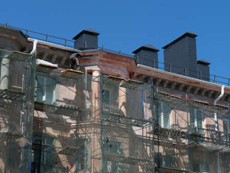 Scaffolding around a building, renovating facade building Фото со стока